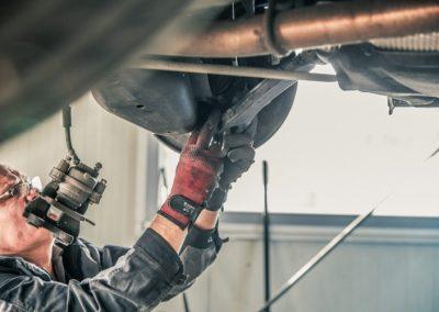 Mitarbeiter repariert ein Auto auf einer Hebebühne